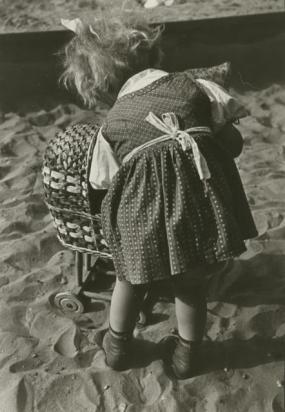 Back view of young girl with toy pram, Erich Retzlaff, ca. 1943, © Estate of Erich Retzlaff